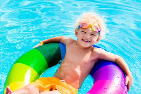 Happy little boy playing with colorful inflatable ring in outdoor swimming pool on hot summer day. Kids learn to swim. Child water toys. Children play in tropical resort. Family beach vacation. Stock Photo