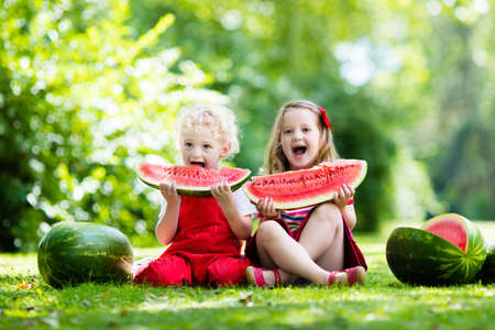 Kind dat watermeloen in de tuin. Kinderen eten fruit buiten. Gezonde snack voor kinderen. Meisje en jongen spelen in de tuin bijten een stukje watermeloen. Stockfoto