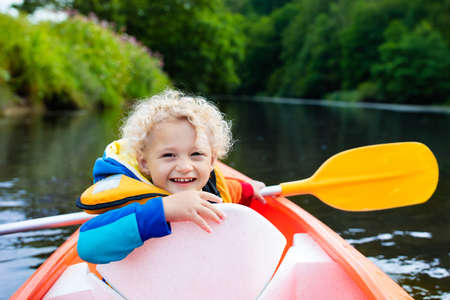 child sport: Happy kid enjoying kayak ride on beautiful river. Little curly toddler boy kayaking on hot summer day. Water sport and camping fun. Canoe for children. Funny child with vessel in a boat. Stock Photo