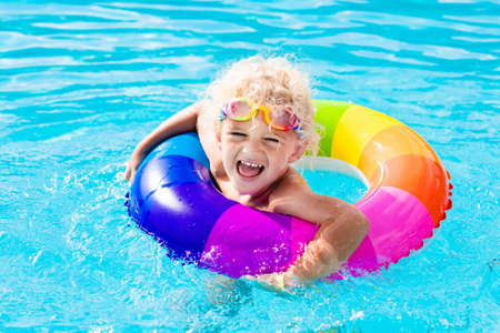 hot day: Happy little boy playing with colorful inflatable ring in outdoor swimming pool on hot summer day. Kids learn to swim. Child water toys. Children play in tropical resort. Family beach vacation. Stock Photo