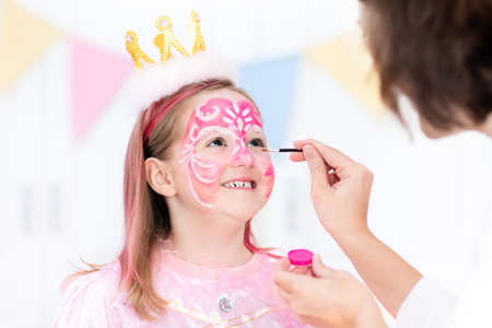 Face painting for little girl. Princess and fairy theme birthday party with face paint artist and costume for preschool child. Kids celebrating Halloween or carnival with pink dress and crown. Stock Photo