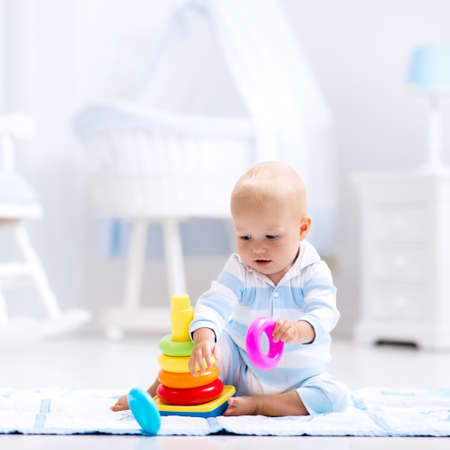 first floor: Cute baby playing with colorful rainbow toy pyramid sitting on play mat in white sunny bedroom. Toys for little kids. Interior for little boy nursery. Child with educational toy. Early development.