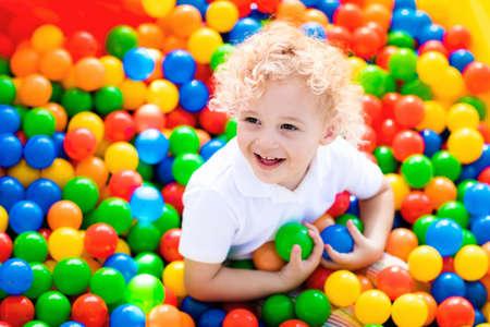 Gelukkige lachende jongen die pret in balkuil op verjaardagspartij hebben in jonge geitjespretpark en binnenspeelcentrum. Kind het spelen met kleurrijke ballen in de pool van de speelplaatsbal. Activiteitenspeelgoed voor kleine kinderen.