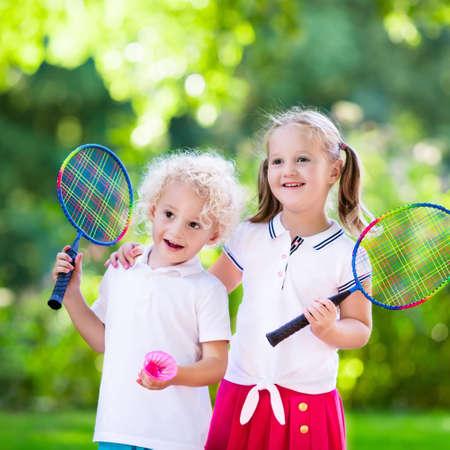 활성 유치원 소녀와 소년 여름에 야외 법정에서 배드민턴 재생. 아이들은 테니스를합니다. 어린이를위한 학교 운동. 어린이 운동 선수를위한 라켓 및