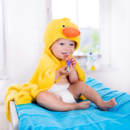 diaper changing table: Little baby in yellow duck towel brushing teeth on changing table after bath. Infant boy with tooth brush. Dental hygiene, toothbrush and toothpaste for young kids. Child teeth and oral health care. Stock Photo