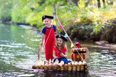 Kinderen gekleed in piratenkostuums en hoeden met schatborst, kijkers, en zwaarden die op houten vlot spelen die in een rivier op hete de zomerdag varen. Pirates rollenspel voor kinderen. Waterplezier voor het gezin. Stockfoto - 75009721