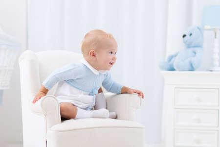 Adorable petit garçon jouant en blanc chambre ensoleillée. Enfant heureux de détente dans le fauteuil de jouets sur le tapis de jeu. Nursery et salle de jeux pour les jeunes enfants. meubles pour bébés, vêtements, textiles et de la literie pour les enfants.