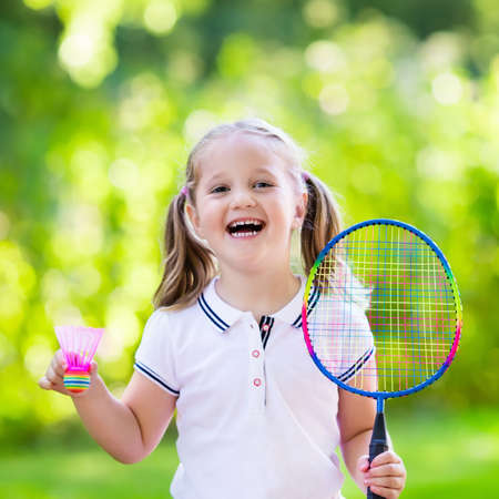 Active preschool girl playing badminton in outdoor court in summer. Kids play tennis. School sports for children. Racquet and shuttlecock sport for child athlete. Kid with racket and shuttle.