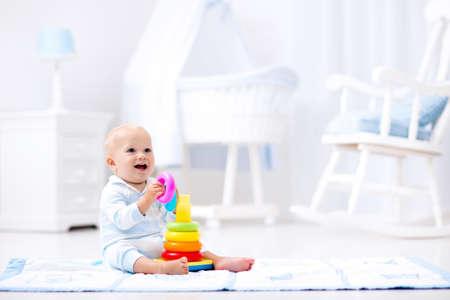 bebe sentado: Bebé lindo que juega con el juguete pirámide de colores del arco iris que se sienta en la estera de juego en blanco soleado dormitorio. Juguetes para niños pequeños. Interior de vivero poco chico. Niño con el juguete educativo. Desarrollo temprano.