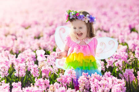 Beautiful girl playing in blooming hyacinth flower field. Kids princess birthday party with fairy costume, butterfly wings and magic wand. Children play in spring flowers. Child picking hyacinths.