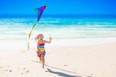 Gelukkig lachend meisje vliegt een kleurrijke vlieger rennen en springen in zand op prachtige tropische strand tijdens een actieve zomer familie zee vakantie. Kinderen spelen op de oceaan wal. Kind met strand speelgoed.