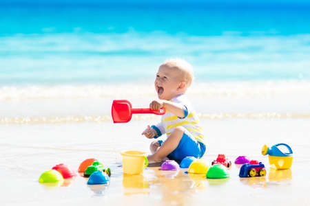 Cute laughing baby boy wearing sun protection rash guard playing with bucket and shovel on tropical beach during family summer sea vacation. Swimwear and beach toys for kids. Child digging in sand.