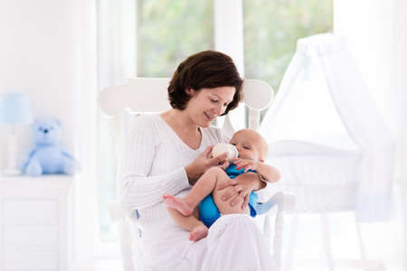 Mother and baby at home. Young woman holding her newborn child sitting in white rocking chair in sunny nursery with crib and garden view window. Parent and kid at home. Infant room interior. Banco de Imagens