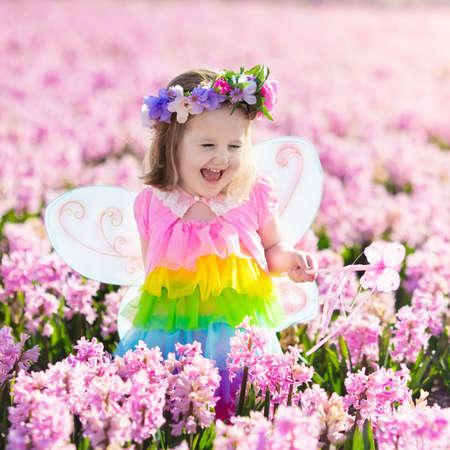 Belle fille jouant dans la floraison champ jacinthe fleur. princesse Kids fête d'anniversaire avec costume de fée, des ailes de papillon et de baguette magique. Les enfants jouent dans les fleurs de printemps. Enfant choisir jacinthes. Banque d'images - 76175750