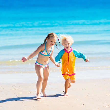 child protection: Happy kids play, run and jump in sand on tropical beach on exotic summer vacation. Boy and girl playing in ocean water. Sea holiday for family with young children. Swim wear for baby and toddler.