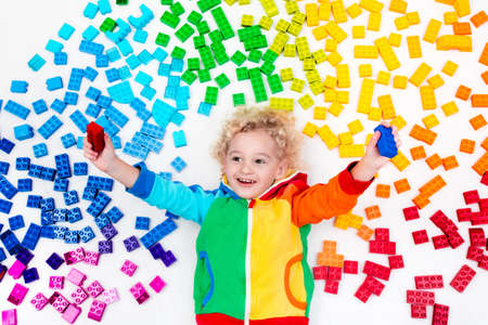 Funny little boy playing with colorful rainbow plastic blocks. Kids play, create and learn colors. Educational toys for creative children. Preschooler building block toys. Kid playing on the floor. Stock Photo