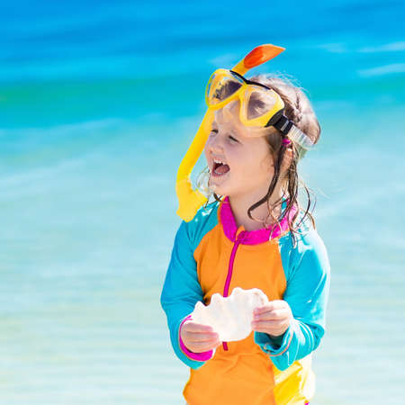 child protection: Happy little girl snorkeling on exotic beach during family summer vacation. Kid with snorkel gear and sea shell at ocean shore on coral island. Child swimming and diving in tropical water. Stock Photo