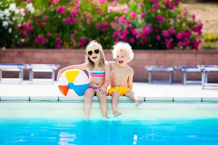 Jonge geitjes die bij buitenzwembad. Meisje en jongen spelen en zwemmen in het zwembad van het resort op tropisch strand eiland zomer familievakantie. Zwem en brillen, bescherming tegen de zon, water speelgoed voor kinderen.