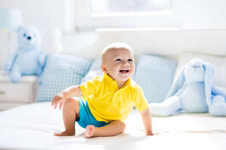 Baby playing on parents bed. Cute funny little boy learning to crawl in white sunny nursery. Infant and toddler room interior. Bedding and toys for kids. Children play at home. Baby bedroom. 写真素材
