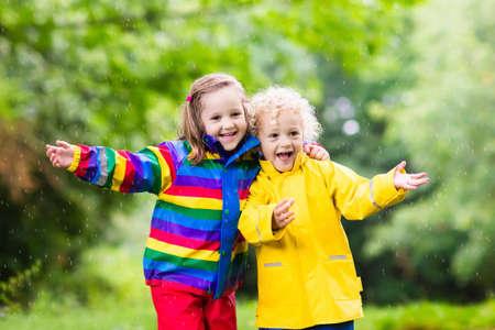 niñas gemelas: niño y niña juegan en el parque de verano lluvioso. Los niños con chaqueta de arco iris de colores y botas de agua saltan en charco de barro y bajo la lluvia. Niños cabina de ducha de otoño. diversión al aire libre por cualquier clima.