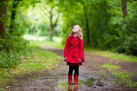 rain weather: Little girl playing in rainy summer park. Child with red ladybug umbrella, waterproof coat and boots jumping in puddle and mud in the rain. Kid walking in autumn shower. Outdoor fun by any weather.
