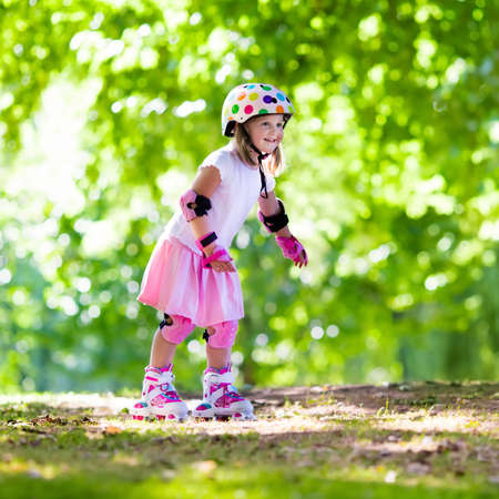 Little girl learning to roller skate in sunny summer park. Child wearing protection elbow and knee pads, wrist guards and safety helmet for safe roller skating ride. Active outdoor sport for kids. Stock Photo
