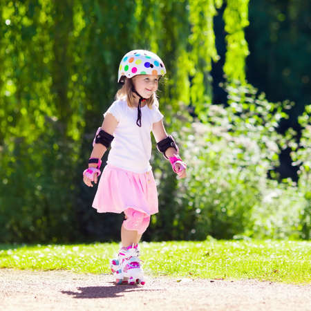 elbow pads: Little girl learning to roller skate in sunny summer park. Child wearing protection elbow and knee pads, wrist guards and safety helmet for safe roller skating ride. Active outdoor sport for kids. Stock Photo