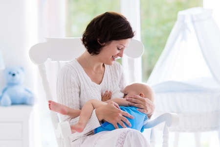 Mother and baby at home. Breastfeeding and healthy infant nutrition. Young woman nursing her newborn child sitting in white rocking chair in sunny nursery with crib and window. Parent and kid at home. 版權商用圖片