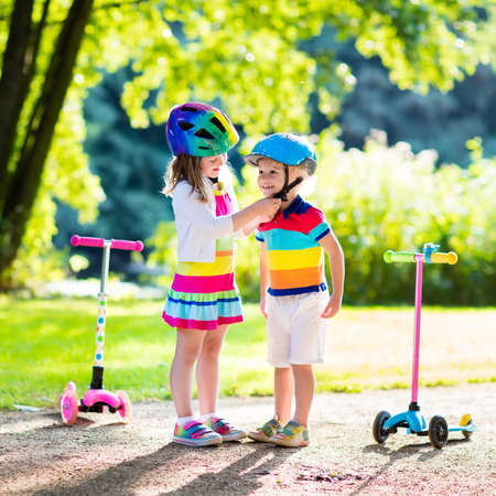 child sport: Children learn to ride scooter in a park on summer day. Preschooler girl helping boy to put on safety helmet. Siblings riding roller. Kids play outdoors with scooters. Active outdoor sport for child. Stock Photo