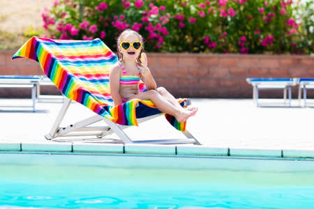 Child eating ice cream at swimming pool. Little girl relaxing in colorful chair at outdoor pool of exotic tropical resort during family summer beach vacation. Kids swim and eat healthy snack. Stock Photo - 77079453