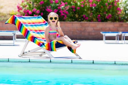 Niño comiendo helado en la piscina. Niña que se relaja en silla colorida en la piscina al aire libre del centro turístico tropical exótico durante vacaciones de la playa del verano de la familia. Los niños nadan y comen bocadillos saludables. Foto de archivo - 77079453