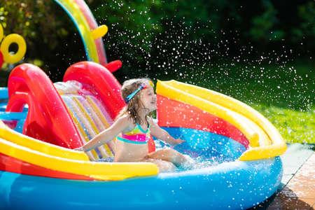 膨脹可能な赤ん坊のプールで遊ぶ子供。子供たちが泳ぐ、スライドとカラフルな庭の中をジャブジャブ遊ぶセンター。幸せな小さな女の子をスライ