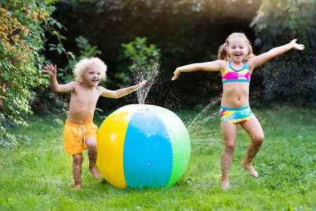 子供おもちゃボール、庭のスプリンクラーで遊ぶ。未就学児の子供の実行とジャンプ。裏庭で夏の屋外水楽しみ。子供たちは、花に水をまくホース