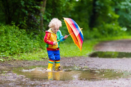 rain weather: Little boy playing in rainy summer park. Child with colorful rainbow umbrella, waterproof coat and boots jumping in puddle and mud in the rain. Kid walking in autumn shower. Outdoor fun by any weather Stock Photo