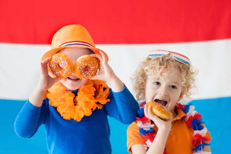 Little Dutch boy and girl wearing country symbols eating orange donuts celebrating King day. Children support Holland sport team. Kids from the Netherlands. Young sport fans with national flag. Stock Photo