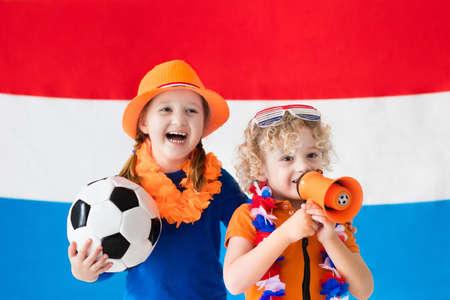 Kinderen juichen en te ondersteunen Nederlands elftal. Kids fans en supporters van Nederland tijdens het voetbalkampioenschap. De jongen en het meisje uit Holland met de nationale vlag en land symbolen. Stockfoto - 77079595