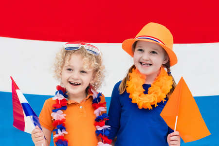 Little Dutch boy and girl wearing country symbols celebrating King day. Children support Holland sport team. Kids from the Netherlands. Young sport fans with national flag. Stock Photo