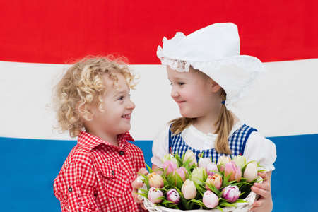 Little Dutch girl and boy wearing traditional national costume, dress and hat holding basket of tulips at flag of the Netherlands. Children with souvenirs from Holland. Kids with tulip flowers. Stock Photo