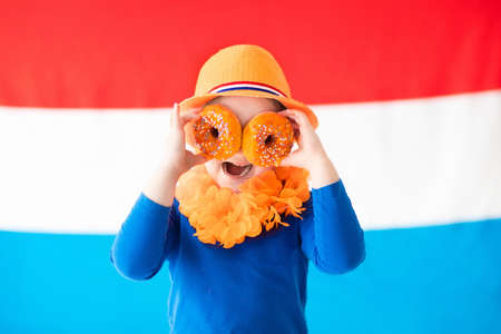 Little Dutch boy girl wearing country symbols eating orange donuts celebrating King day. Children support Holland sport team. Kids from the Netherlands. Young sport fans with national flag. Stock Photo