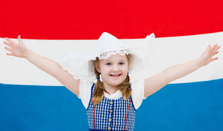 dutch girl: Little Dutch girl wearing traditional national costume, dress and hat with flag of the Netherlands celebrating King?s day. Child with souvenirs from Holland. Kid fan of Holland sport team. Stock Photo