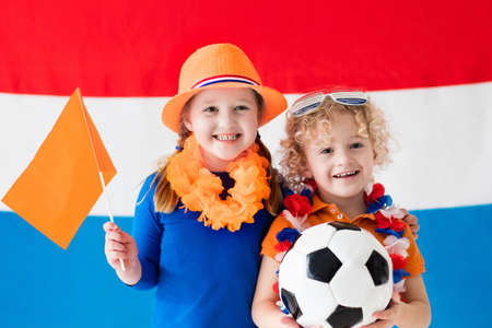 Children cheering and supporting Dutch football team. Kids fans and supporters of the Netherlands during soccer championship. Boy and girl from Holland with national flag and country symbols.
