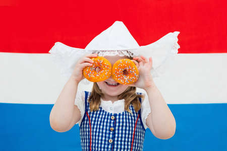 dutch girl: Little Dutch girl wearing traditional national costume, dress and hat holding orange donuts at flag of the Netherlands. Child with Oranje souvenirs from Holland celebrating King day. Kid with sweets.