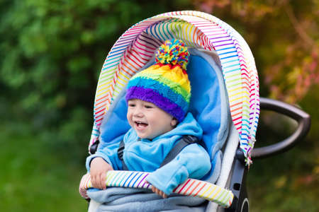 stroll: Baby in stroller on a walk in autumn park. Adorable little boy with knitted hat and jacket sitting in colorful pushchair under warm blanket. Fall outdoor fun for kids. Child in buggy on winter stroll. Stock Photo