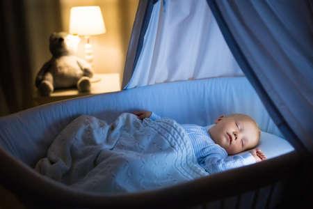 Schattige baby het drinken van melk in blauwe mandewieg met luifel 's nachts. Kleine jongen in pyjama met formule fles klaar om te slapen in een donkere kamer met een wieg, lamp en speelgoed beer. Bedtijd drank voor kinderen. Stockfoto - 77079697