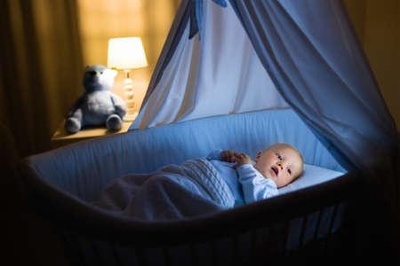 かわいい赤ちゃんが夜天蓋付き青バシネットで牛乳を飲みます。ベビーベッド、ランプ、おもちゃのクマと暗い部屋で寝る準備式のボトルとパジャマの少年。子供のためのベッド時間ドリンク。 写真素材 - 77079764