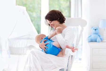 Mutter und Kind zu Hause. Junge Frau im weißen Schaukelstuhl ihr neugeborenes Kind hält in sonnigen Kindergarten mit Krippe und Blick auf den Garten Fenster sitzen. Elternteil und Kind zu Hause. Infant Innenraum.
