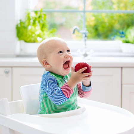 bebe sentado: Baby eating fruit. Little boy biting apple sitting in white high chair in sunny kitchen with window and sink. Healthy nutrition for kids. Solid food for infant. Snack or breakfast for young child.