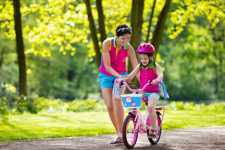 Child riding bike. Kid on bicycle in sunny park. Mother teaching little girl to cycle. Preschooler learning to balance wearing safe helmet. Sport for parents and kids. Family outdoor on bike ride. Stock Photo