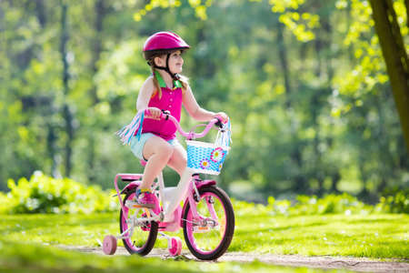 Child riding bike. Kid on bicycle in sunny park. Little girl enjoying bike ride on her way to school on warm summer day. Preschooler learning to balance on bicycle in safe helmet. Sport for kids. Stock Photo