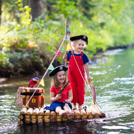 Kids dressed in pirate costumes and hats with treasure chest, spyglasses, and swords playing on wooden raft sailing in a river on hot summer day. Pirates role game for children. Water fun for family. Imagens